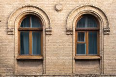 两葡萄酒成拱形在黄色砖墙壁的窗口  绿色-海在一褐红深红木的波浪玻璃的颜色 免版税库存照片