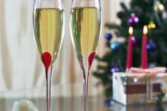 两葡萄酒杯用香槟、圣诞节云杉、礼物和蜡烛 库存照片