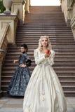 两葡萄酒礼服的美丽的妇女在自然 免版税库存照片