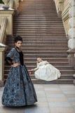 两葡萄酒礼服的美丽的妇女在自然 库存照片