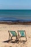 两蓝色和在沙子的白色镶边海滩睡椅靠岸与它的往照相机的后面 免版税库存图片