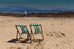 两蓝色和在沙子的白色镶边海滩睡椅靠岸与它的往照相机的后面 免版税库存照片