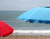 两蓝色和在海滩的红色沙滩伞 库存图片