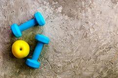 两蓝色重量、哑铃和黄色苹果在具体背景 免版税图库摄影