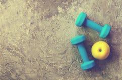 两蓝色重量、哑铃和黄色苹果在具体背景 免版税库存图片