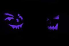 两蓝色雕刻了发光在万圣夜黑色背景的南瓜的面孔 免版税库存照片