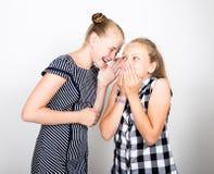 两表现出逗人喜爱的矮小的女朋友不同的情感 滑稽的孩子 最好的朋友纵容和摆在 库存照片