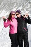 两装备了拥抱在一座高冬天山的远足者妇女 姐妹 免版税库存图片
