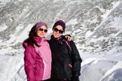 两装备了拥抱在一座高冬天山的远足者妇女 姐妹 库存照片