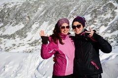 两装备了拥抱在一座高冬天山的远足者妇女 姐妹 库存图片