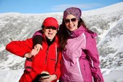 两装备了拥抱在一座高冬天山的远足者妇女 母亲和女儿 库存图片