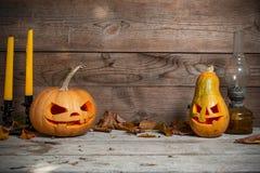 两装饰了南瓜在神秘的秋天背景的万圣夜与蜡烛和煤气灯 免版税库存照片