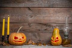 两装饰了南瓜在神秘的秋天背景的万圣夜与蜡烛 免版税库存图片