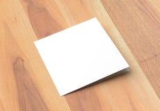 两褶的方形的小册子嘲笑在木背景 3D illustra 免版税库存图片