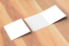 两褶的方形的小册子嘲笑在木背景 3D illustra 免版税库存照片