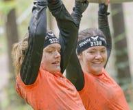 两设法微笑的妇女维护她的在一条自由散漫的绳索的平衡 免版税库存照片