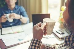 两谈话和喝在候选会议地点的商人在办公室 免版税库存图片