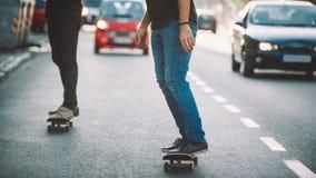 两赞成滑板车手乘驾冰鞋通过在街道上的汽车 免版税库存照片