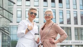 两走在街道上的女实业家在大厦附近 去与片剂计算机一起的女商人 影视素材