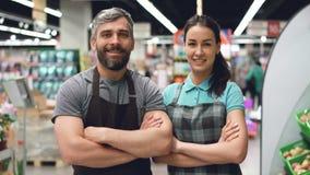 两超级市场雇员可爱的人画象站立里面商店,微笑和看照相机的围裙的 股票视频