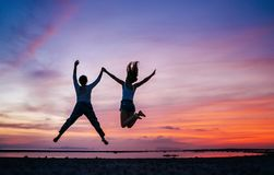 两跑和日落海海滩的跳跃的女朋友 手拉手概念图象 库存图片