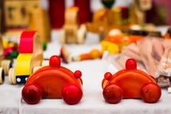 两辆五颜六色的木汽车 螺纹将扯拽的葡萄酒玩具 库存照片