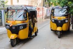 两辆去由街道的印地安moto人力车tuk tuk Puttaparthi 2月11日2018年,印度 免版税库存照片