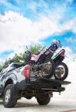 两辆土自行车摩托车在有saf的camo卡车背面 免版税库存图片