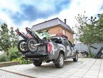 两辆土自行车摩托车在d的camo卡车背面 免版税库存照片