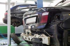 两辆汽车在汽车维修车间的修理 免版税库存图片