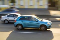 两辆汽车快速地移动沿干净的城市道路的蓝色和灰色在明亮的晴天 大厦和树被弄脏的背景  速度 免版税图库摄影