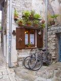 两辆自行车停放了在一个窗口下在老镇 免版税库存照片