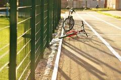 两辆自行车在体育场的柏油路 绿色篱芭栅格在草坪领域的背景的 库存图片