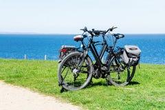两辆自行车在草坪停放了在宽蓝色海 免版税图库摄影