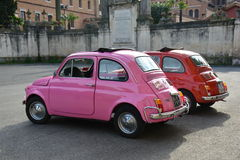 两辆菲亚特Cinquecento汽车绘与明亮的桃红色和红颜色在罗马停放了 库存图片