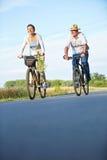 两辆资深人民乘坐的自行车在夏天 免版税库存图片