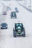 两辆除雪机和汽车在暴风雪期间 免版税图库摄影