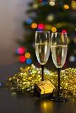 两透明杯与泡影的香槟在闪亮金属片或sequinswo背景中  免版税库存图片