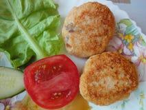 两道炸肉排、莴苣的叶子,一个蕃茄和一个黄瓜在白色板材/准备好午餐/服务了盘用食物/ 免版税库存照片