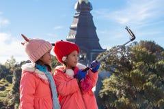两采取在手机的逗人喜爱的亚裔儿童女孩selfie,当享受他们的假期假日时 免版税库存照片