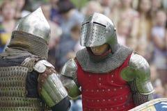 两钢盔甲的中世纪骑士在被弄脏的背景 库存图片
