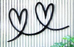 两钢黑心形垂悬在与绿色植物的老锌墙壁背景 库存图片