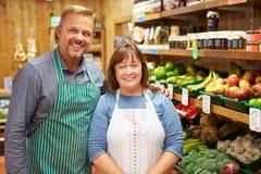 两销售辅助在农厂商店菜柜台  免版税库存照片