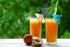 两长的杯与一把蓝色和红色伞的桃子汁 免版税库存图片