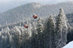 两间橙色客舱空中览绳和积雪的云杉的树看法  免版税图库摄影