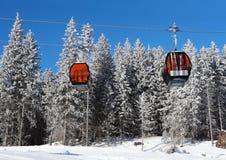 两间缆车客舱和积雪的云杉的树在滑雪关于 免版税库存图片
