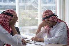 两阿拉伯人商人举行手在被注重的手上不犯在他们的和事务的错误与膝上型计算机一起使用 库存照片