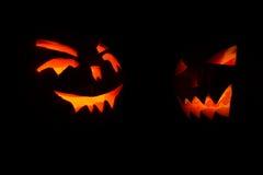 两雕刻了发光在万圣夜黑色背景的南瓜的面孔 库存图片