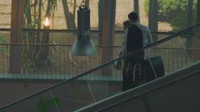 两青年人乘坐在带着手提箱的自动扶梯下的,从蜜月的新婚佳偶 影视素材