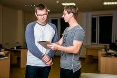 两青年人在办公室谈论项目 站立紧挨着,他们中的一个告诉其他关于他的projec 库存照片